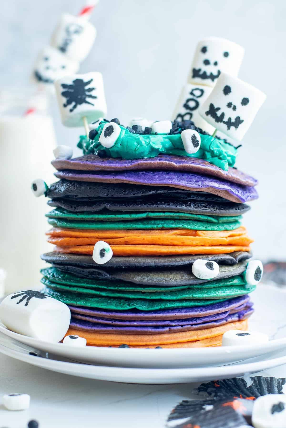 Stack of multi-colored halloween pancakes with decorated marshamallows.