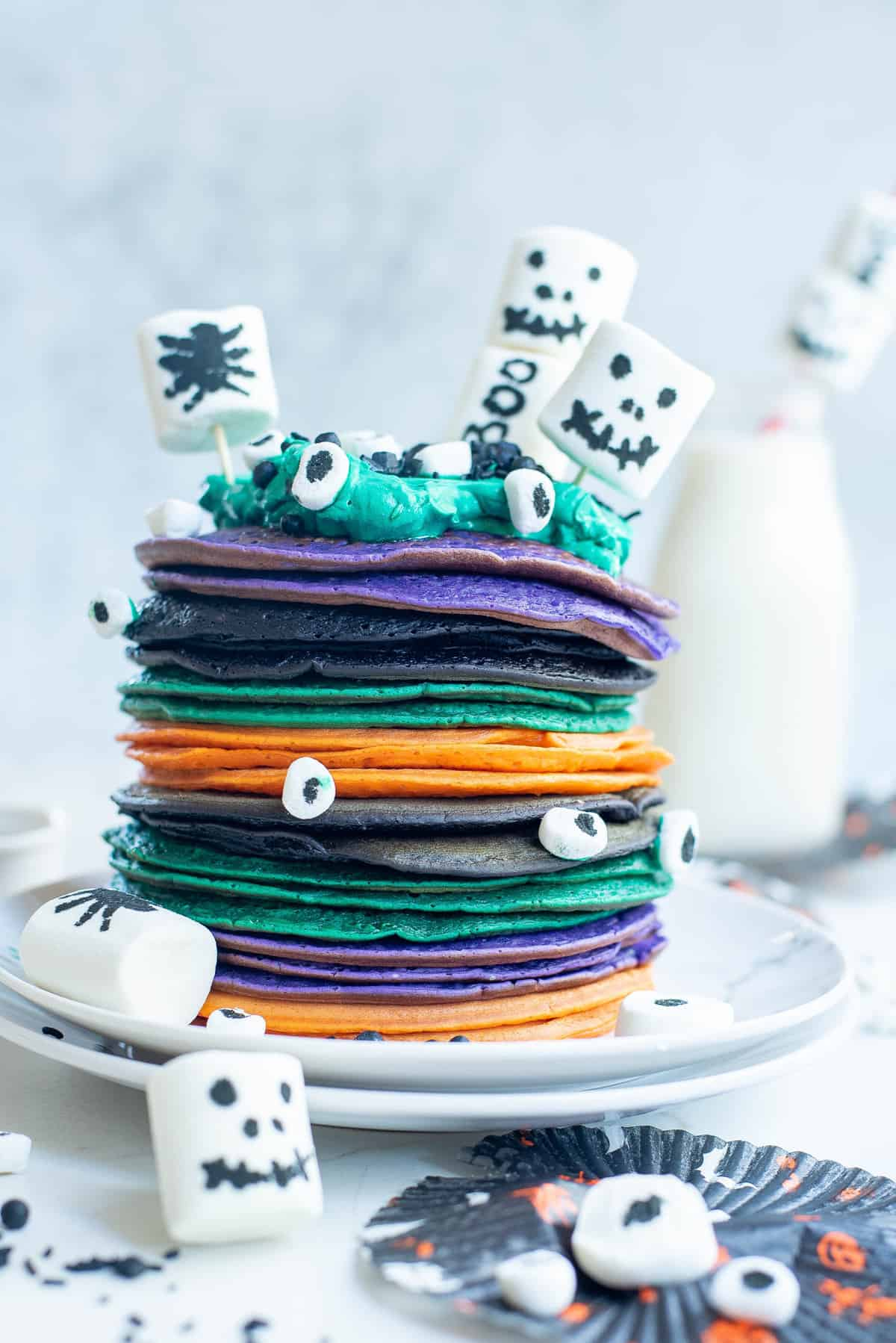 Green, orange, purple, and black pancakes in stack, decorated with marshmallows.