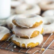 Three pumpkin donuts with white glaze, stacked up on cooling rack.