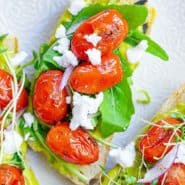 Avocado toast topped with arugula, feta, roasted tomatoes, and red onion.