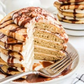 Tiramisu pancakes stacked up with layers of mascarpone filling and a kahlua drizzle.