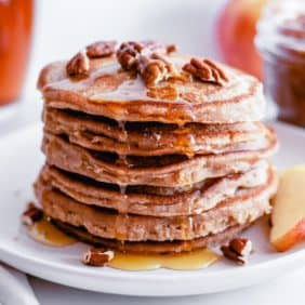 Stack of apple butter pancakes dripping with syrup and topped with pecans.