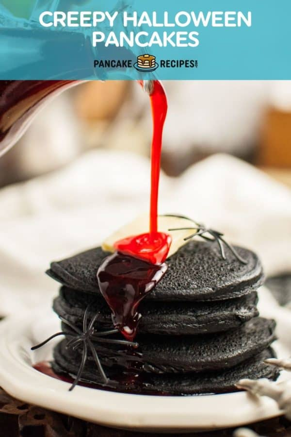 """Stack of black pancakes with red syrup, text overlay reads """"creepy halloween pancakes."""""""