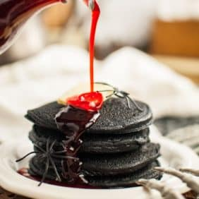 Stack of dark black pancakes topped with butter, a red syrup being poured on top.